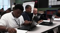 High School students are working on their computers. A teacher is helping them.
