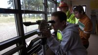 Student is looking through a camera in one of their field trip.