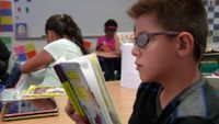 Student is reading a book in a classroom.