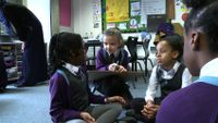 Primary students are talking in a group work together