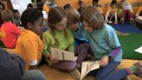 A group of primary school students are reading and working together.