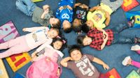 Group of Pre-K kids lying in a circle with their heads touching.
