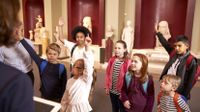 Group of students raising their hands during a museum field trip.