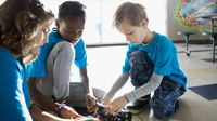 Three elementary students work on a robotics project together