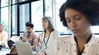 Focused teacher with laptop listening in professional development meeting.