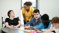 Special education teacher working with high school students with various abilities