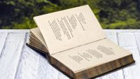 Antique book of poetry sitting on picnic table