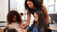 Teacher helping teen students on a tablet