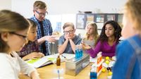 A group of elementary school students working on a science experiment in the classroom.