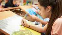 Student making a watercolor painting on a drawing table in art class
