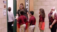 A teacher greeting her students at the door to her classroom