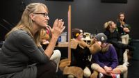 A female teacher is sitting cross-legged on a stage, and students are standing, talking to each nearby in costumes.