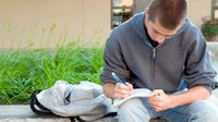 Older boy sitting on a large cement planter in a school courtyard writing in a spiral notebook