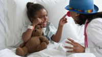 A young girl is lying in a hospital bed, holding a teddy bear, smiling, and pointing at her doctor's face. Her doctor is wearing a clown hat and nose.