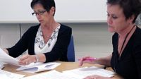 Two teachers working side-by-side at a table covered with papers