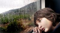 Boy leaning his head against a window sill looking out at the rain