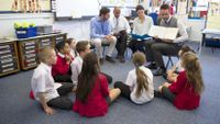 Four adults sit in front of a circle of students—one adult instructs and the other three observe.