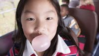 A young girl chews gum on a school bus.