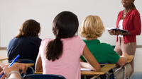 photo of teacher in front of an engaged classroom