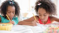 Two girls work on their homework side by side.