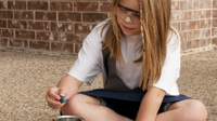 Girl adding blue food coloring to her volcano project