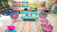 A colorful classroom with couches, collapsible desks, and scoop chairs