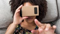 A young woman uses a cardboard virtual reality headset.