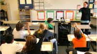 Teacher in front of class pointing to students sitting at desks with raised hands