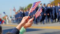 Picture of two people waving small U.S. flags with a memorial day parade in the background