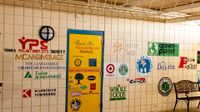 An outdoor covered hallway with 25+ logos painted on the wall and door