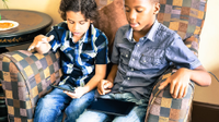A photo of 2 young boys sitting in a big easy chair, playing games on their tablets.