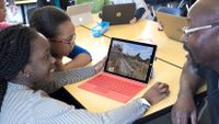 Two girls work in Minecraft in a classroom as a teacher sits with them and talks.