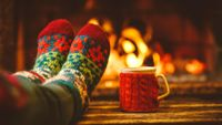 Photo of feet in socks propped up in front of a fire
