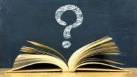 Image of an open book under a question mark written in chalk on a blackboard