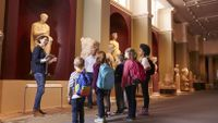 Young students learn while looking at an ancient statue in a museum.