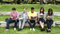 A group of students sit outside taking notes on what they notice about the world around them.