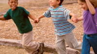 A photo of elementary school children holding hands and laughing.