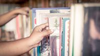 Photo of a bookshelf with students' hands reaching in to make selections