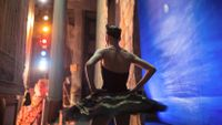 A female ballet dancer standing on the side of a stage about to dance.