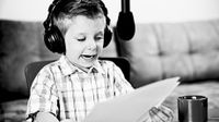 A black and white image of a young boy wearing headphones, reading from papers, speaking into a hanging microphone