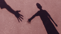 Shadow of two people reaching out their hands to each other