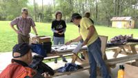 A group of people work on an electrical project at an outdoor picnic table.