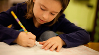 A photo of an elementary-school girl writing in her notebook with a pencil.
