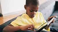 Boy sitting at end of a couch working on a tablet