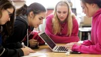 Four girls look at a laptop together in class.