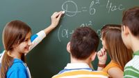 Middle school students discuss math problems written on a blackboard.