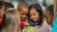 A diverse group of kids look at a globe together.