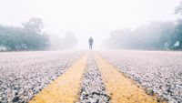 A student stands in the middle of a fog-shrouded road.