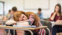A bored student sleeps at her desk.