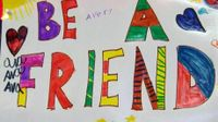 "A poster pinned on the wall drawn by students that says ""Be A Friend"""